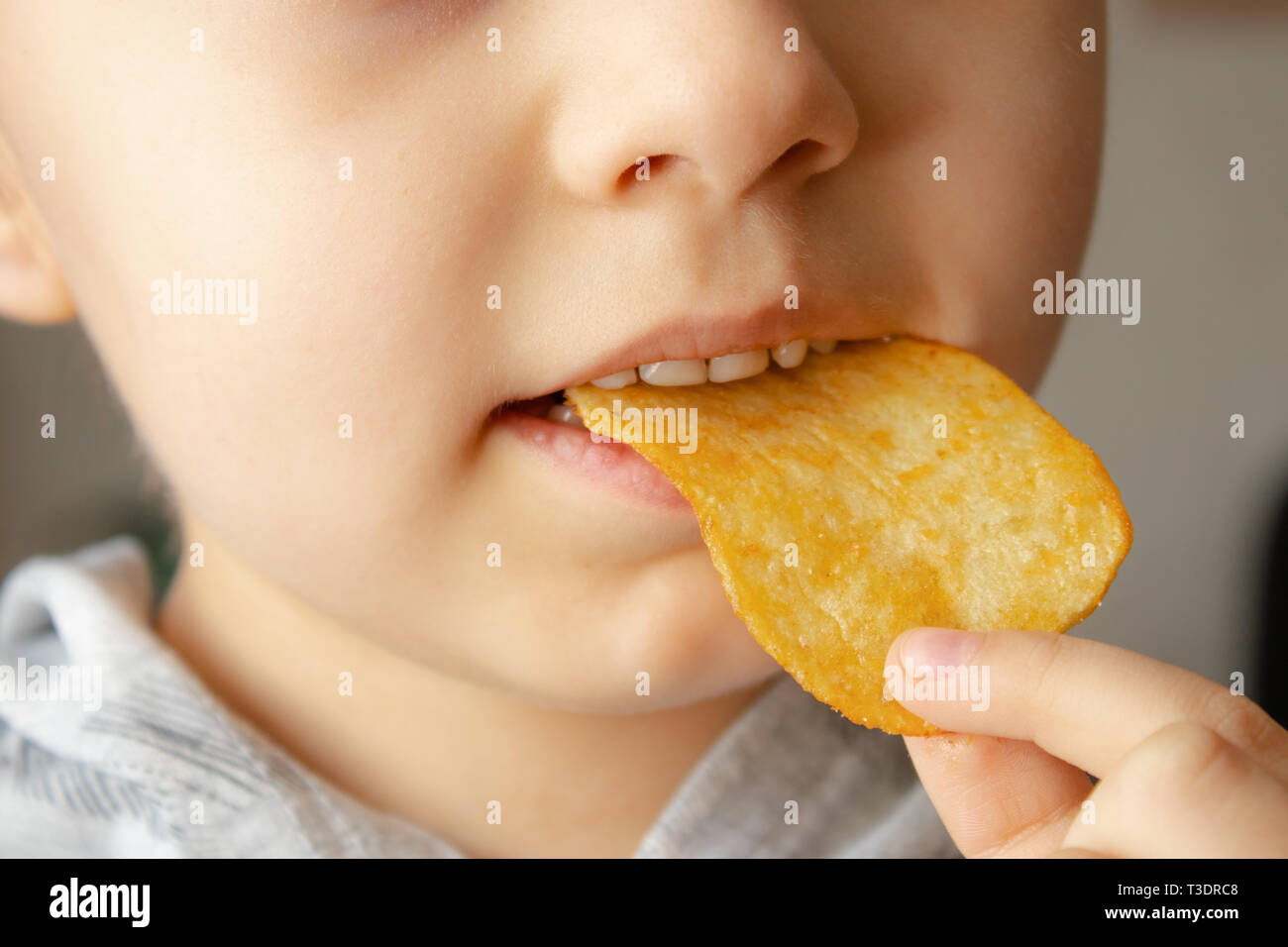 Baby eating chips. Close-up. The child holds the chips. Junk food. - Stock Image