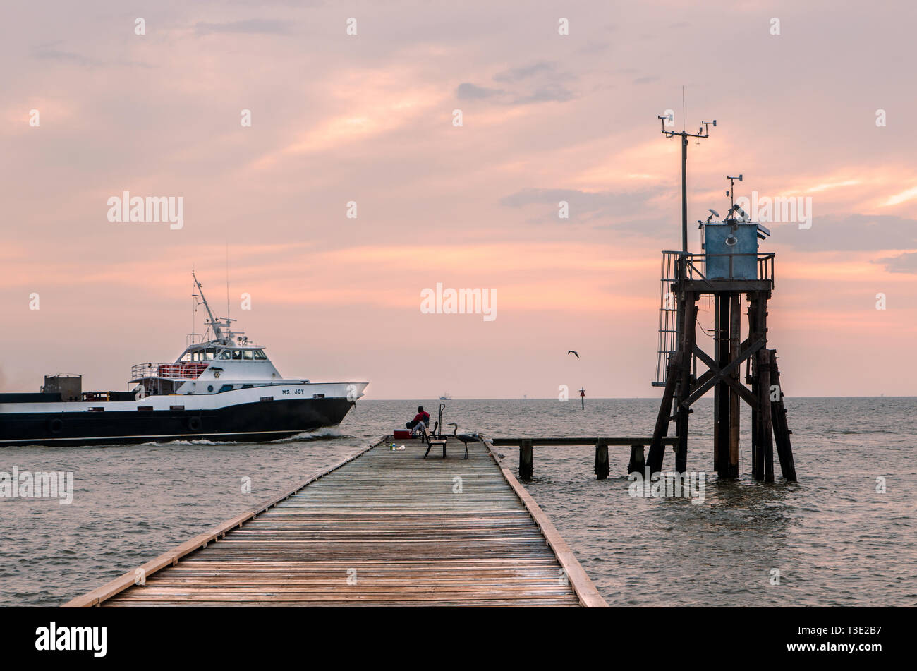 A Boat Passes A Fisherman At The Public Fishing Pier On The East End Of Dauphin Island Alabama Near Fort Gaines Stock Photo Alamy