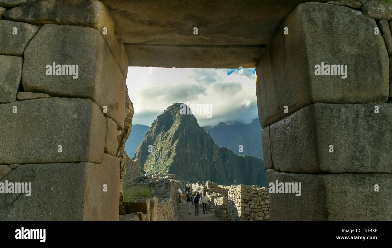 huayna picchu framed by a stone doorway at machu picchu - Stock Image