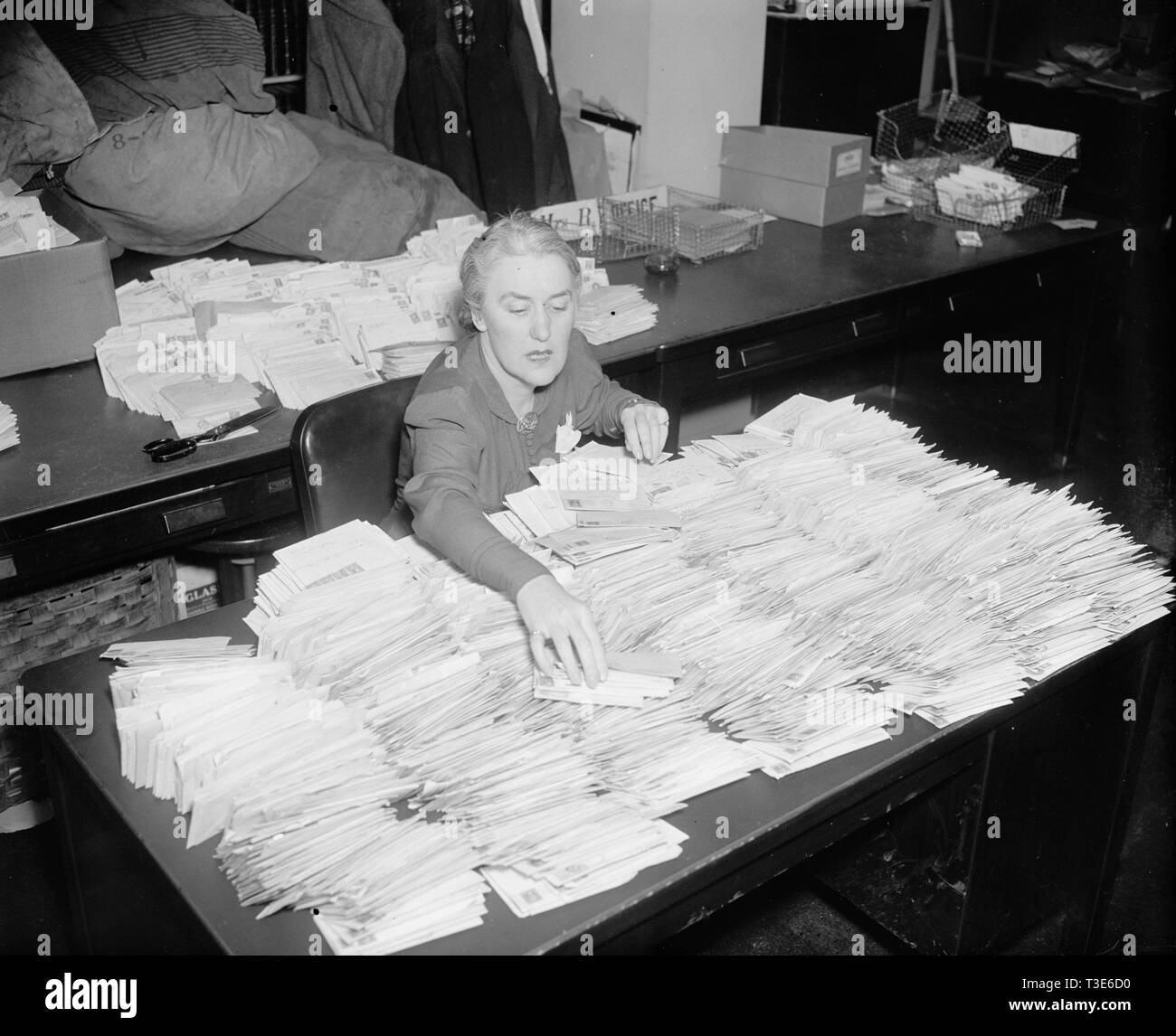 January 28, 1938 - Miss Margaret Lehand, Personal Secretary to President Roosevelt, is shown opening some of the 30,000 letters with donated dimes to the infantile paralysis foundation to arrive in the mail - Stock Image