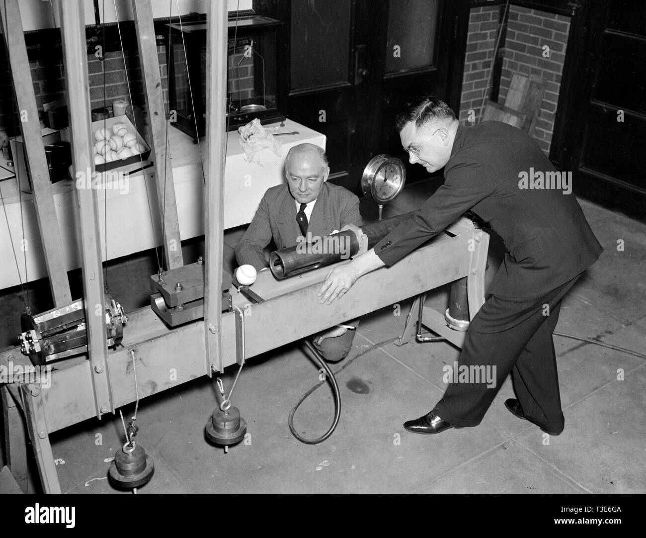 Government Waste - Bureau of Standards designs mechanical batter to determine liveliness of baseballs, an example of government wasting money during the Great Depression ca. 1938 - Stock Image