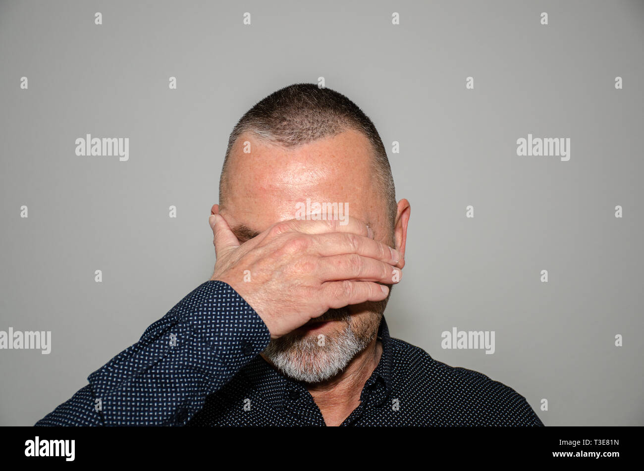 Man covering his eyes with one hand in shame or embarrassment or in a concept of see no evil over a grey studio background - Stock Image