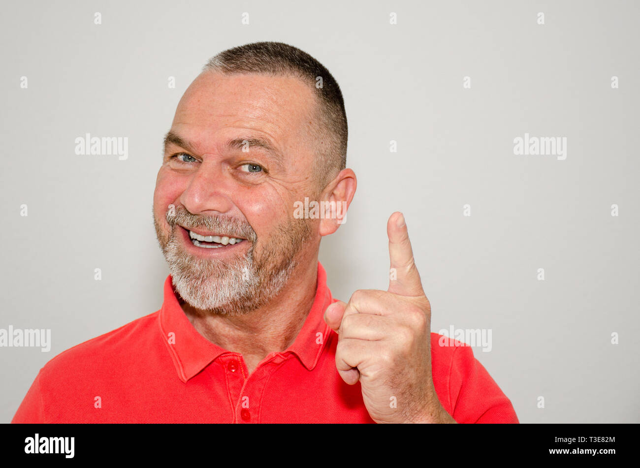 Gleeful happy man in a colorful red shirt with a beaming smile pointing a finger to stress a point over a light grey studio background - Stock Image