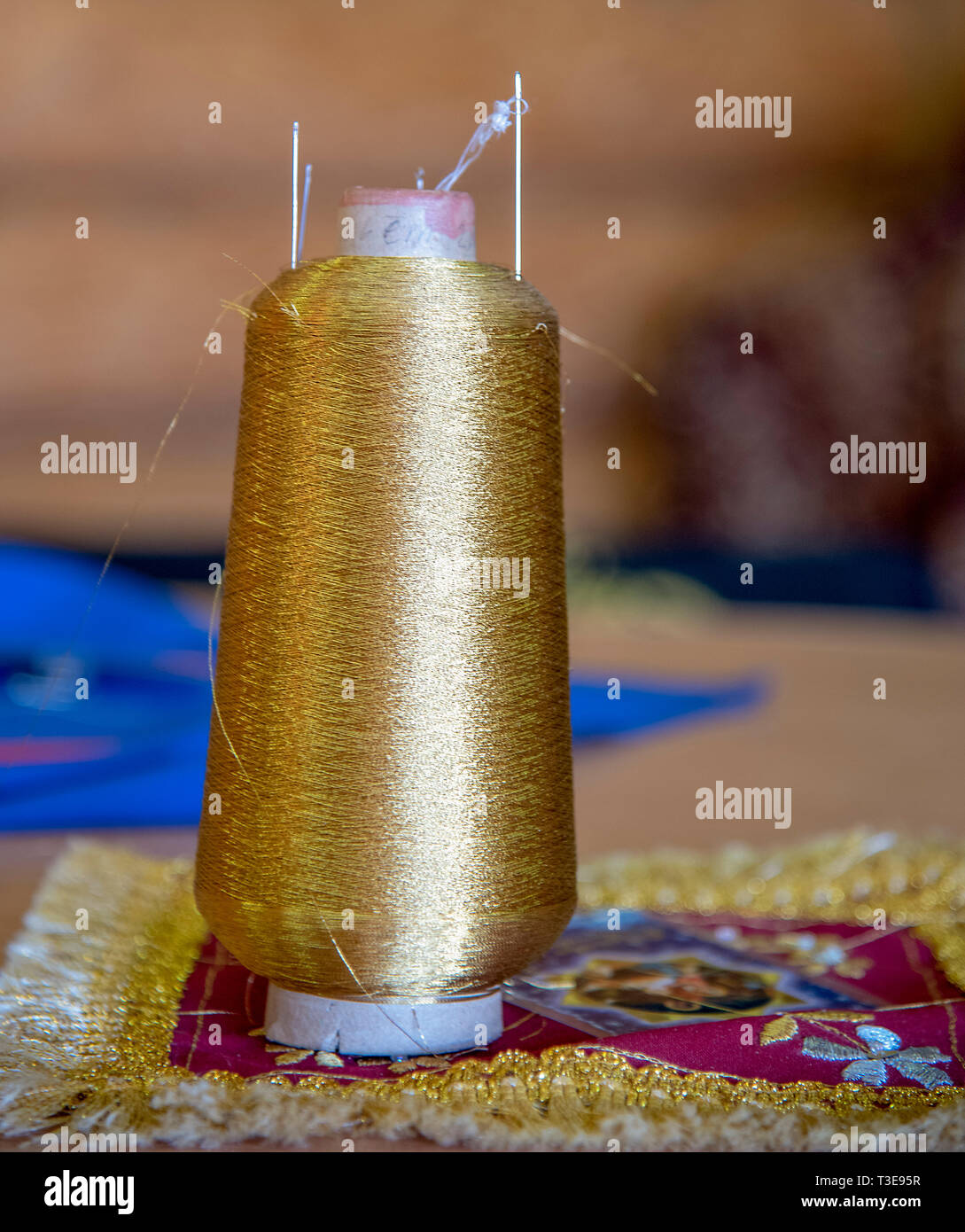 A coil of gold thread stands on the table. The coil is inserted the needle. - Stock Image