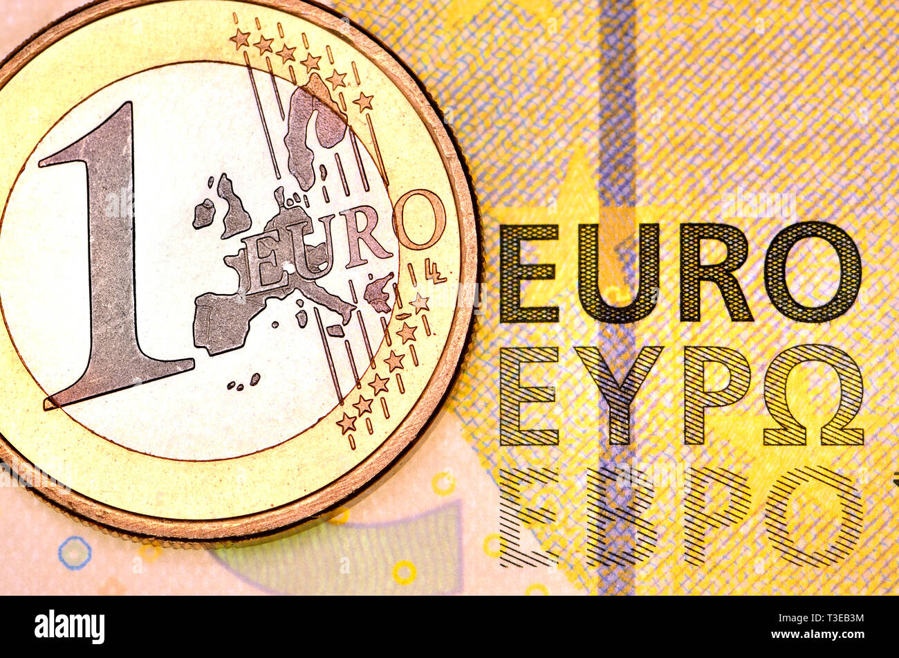 1 Euro coin on a 5 Euro note - Stock Image