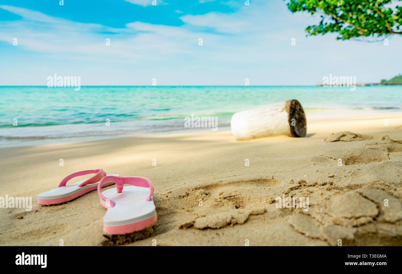 Pink and white sandals on sand beach. Casual style flip-flop were removed at seaside. Summer vacation on tropical beach. Fun holiday travel on sandy b - Stock Image