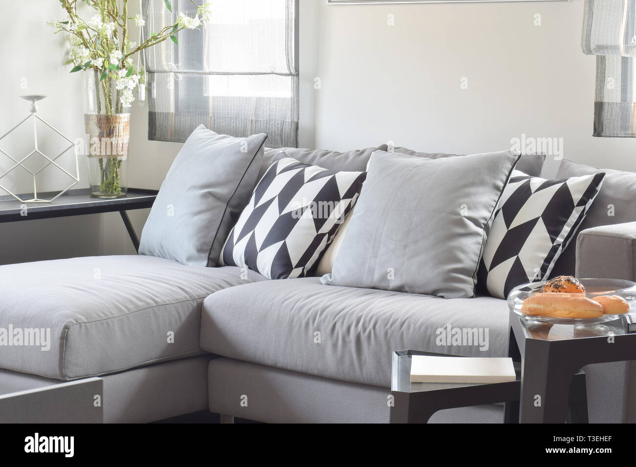 Black and white parallelogram pattern pillows on gray comfy sofa - Stock Image