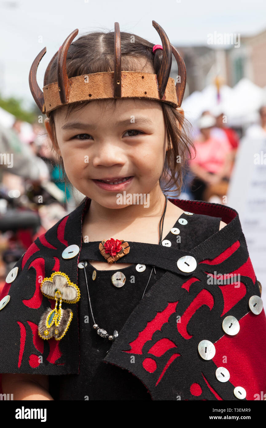 Happy, smiling, Native American child wearing traditional clothing at the Penn Cove Water Festival. Pacific Northwest Haida Tlingit Indian tribes. - Stock Image