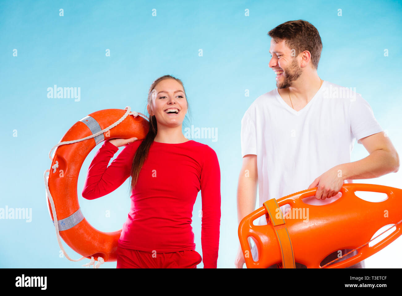 f00eec8c432 Accident prevention and water rescue. Young man and woman lifeguard couple  on duty holding buoy lifesaver equipment on blue