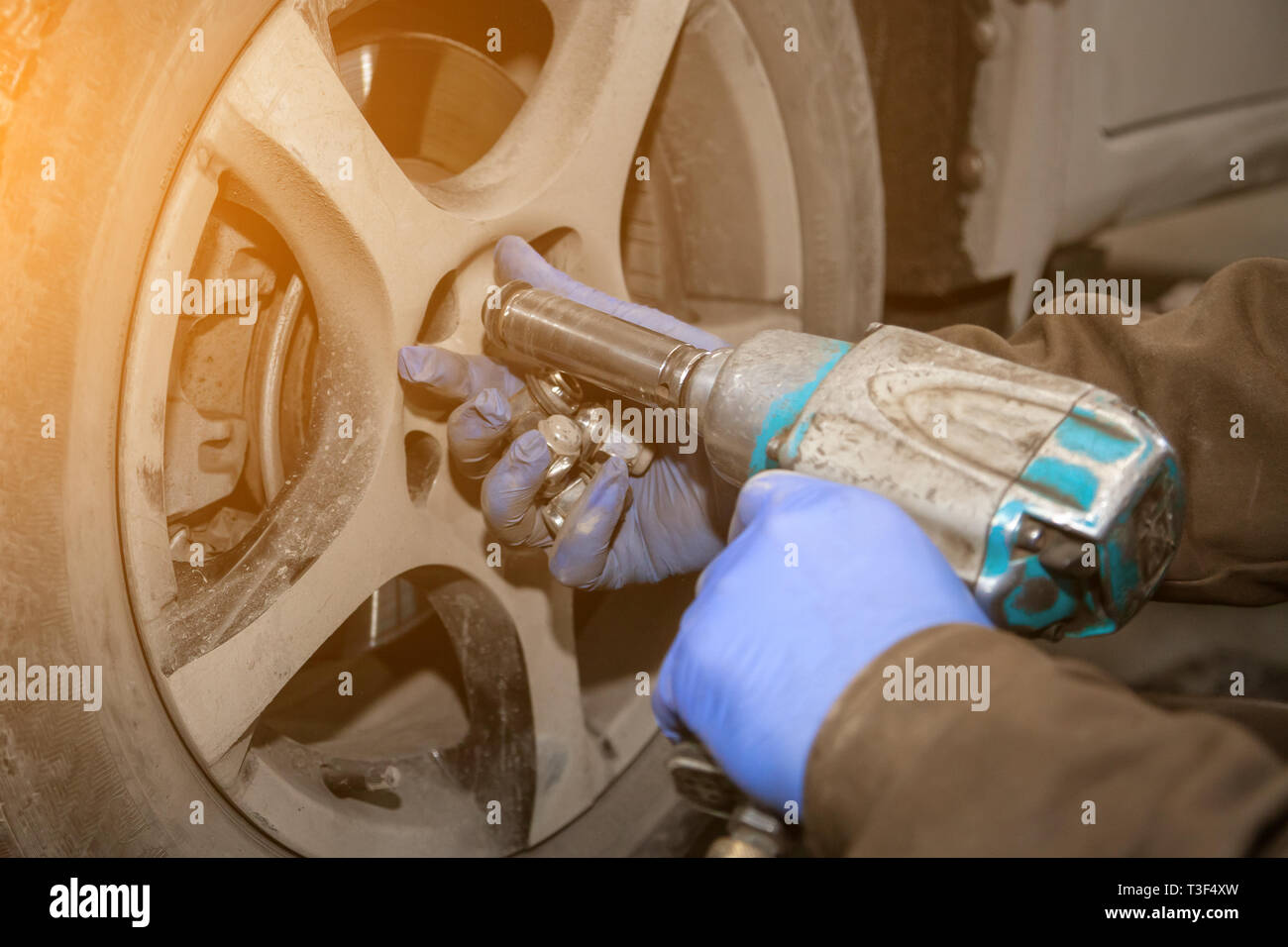 Close up Professional car mechanic changing car wheel in