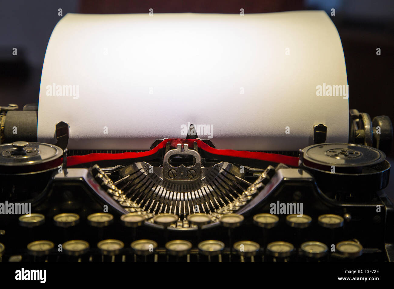 Historical portable typewriter with empty sheet, close up - Stock Image
