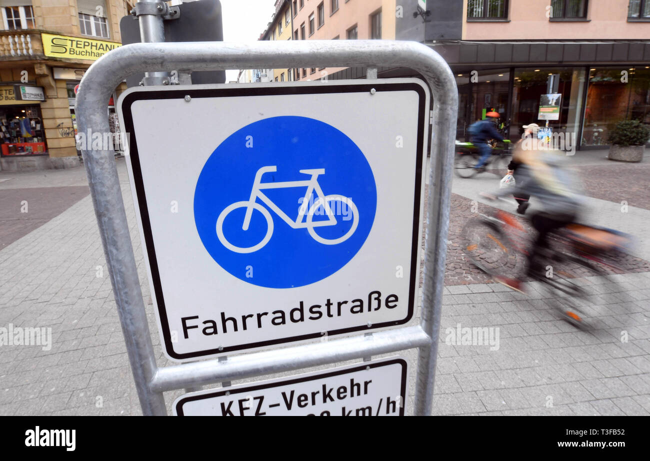 Karlsruhe, Germany. 08th Apr, 2019. In the city centre of Karlsruhe there is a sign of a bicycle street where a cyclist drives past. The Allgemeine Deutschze Fahrrad-Club (ADFC) wants to present how bicycle-friendly Baden-Württemberg's cities are. Credit: Uli Deck/dpa/Alamy Live News - Stock Image