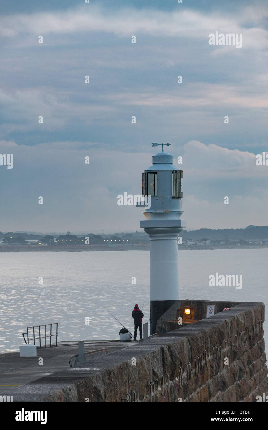 Penzance, Cornwall, UK. 9th Apr, 2019. UK Weather. It was mild and warm for the sunrise at Penzance this morning for this fisherman on the harbour walls at Penzance. Credit: Simon Maycock/Alamy Live News Stock Photo