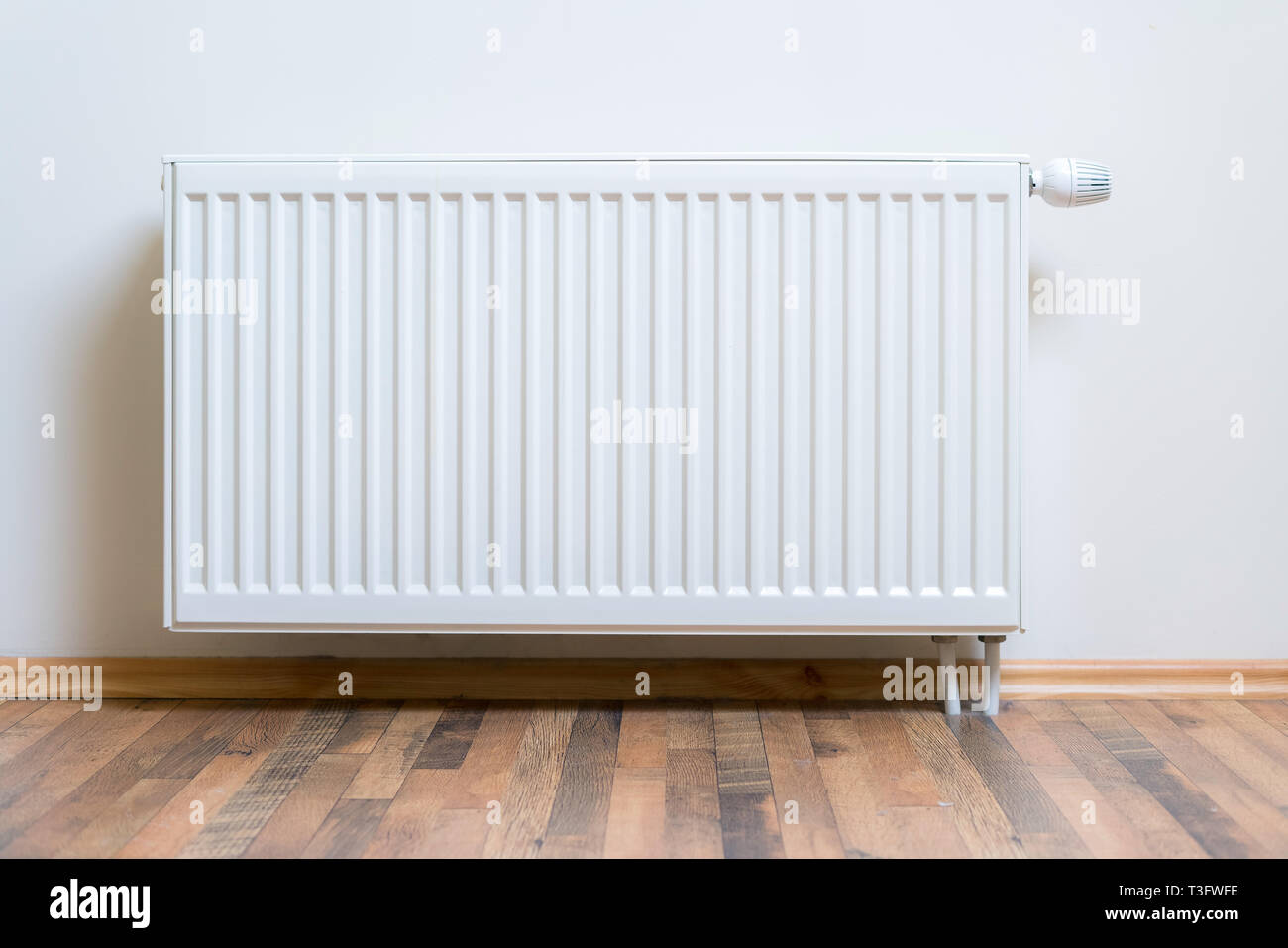 Home radiator heater on the white wall on wooden hardwood floor. Adjustable warming equipment for apartment and home - Stock Image