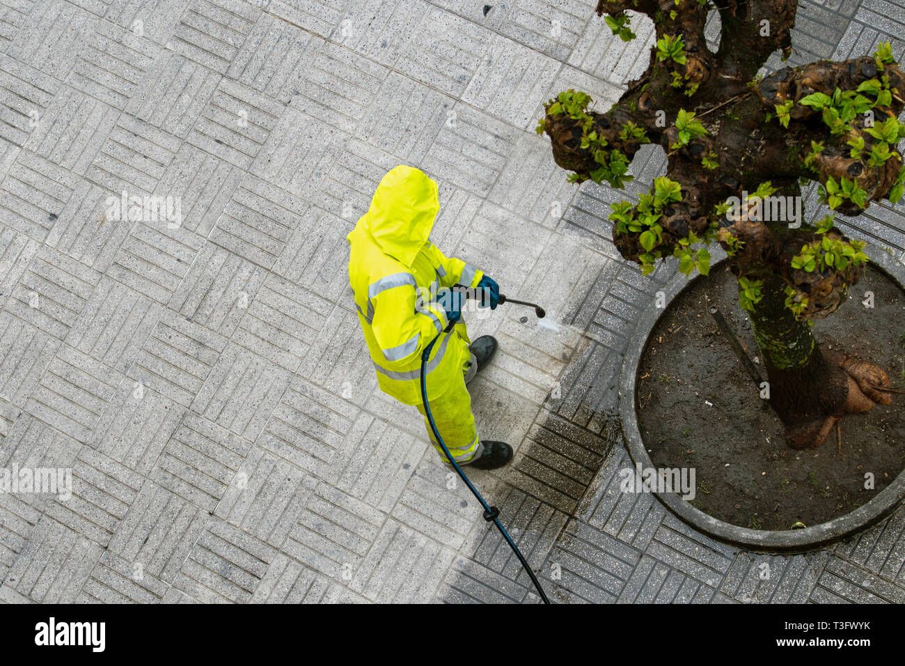 Top view of a Worker cleaning the street sidewalk with high pressure water jet. Public maintenance concept - Stock Image
