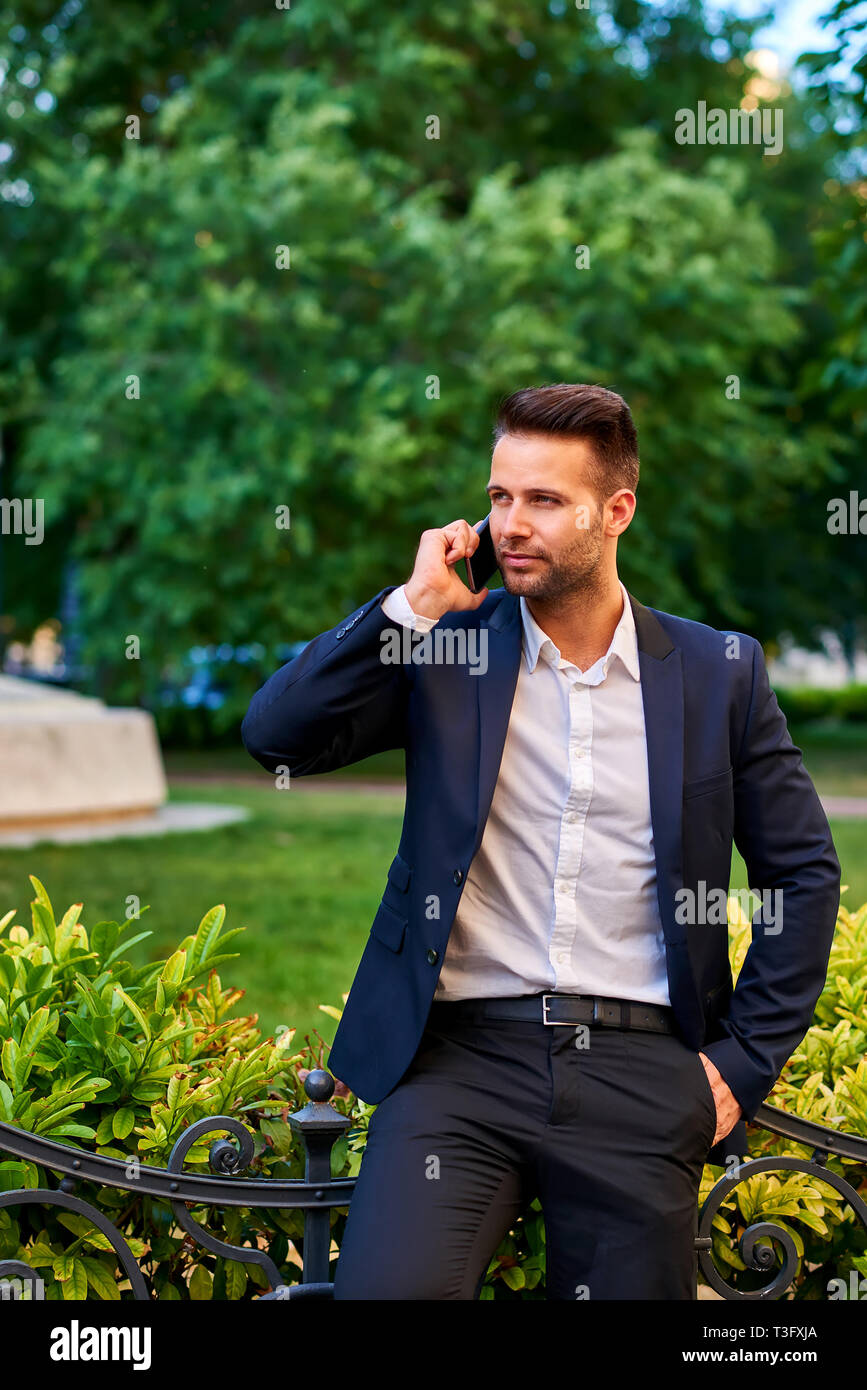 A handsome young businessman leaning against the fence in a park while talking on a phone Stock Photo