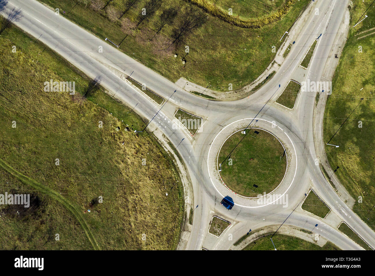 Aerial view of traffic circle roundabout road junction, top view with cars - Stock Image