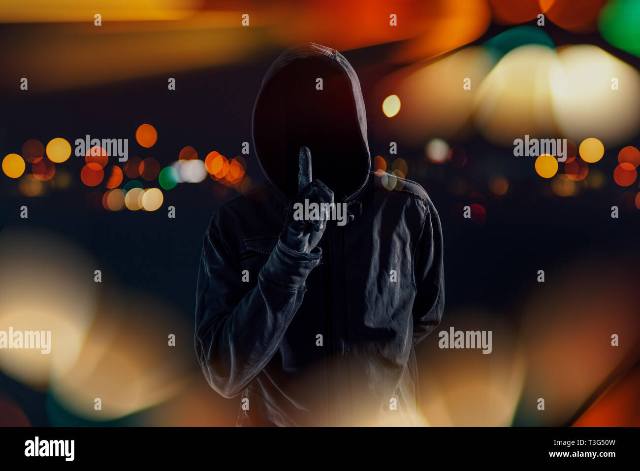 Hooded maniac with finger on lips gesturing shh sign to silence victim before attack - Stock Image