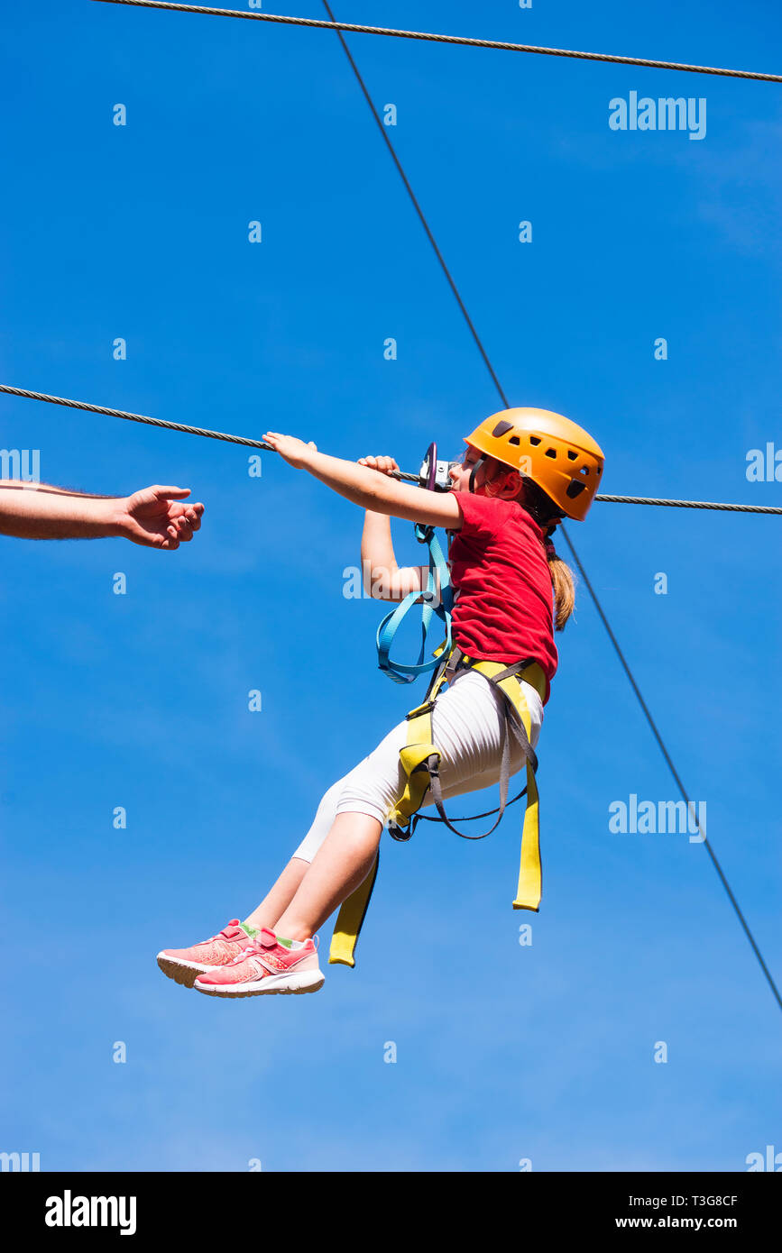 Little brave caucasian girl using a zip line. An indefinited man lend a helping hand. - Stock Image