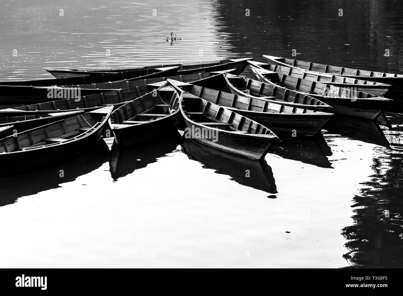 Boats on Phewa lake, Pokhara, Nepal. Black and white image - Stock Image