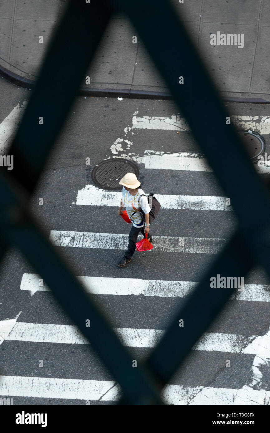 Woman walking along a crosswalk while carrying shopping bags in New York City's Chinatown district in Downtown Manhattan, NYC, NY - Stock Image