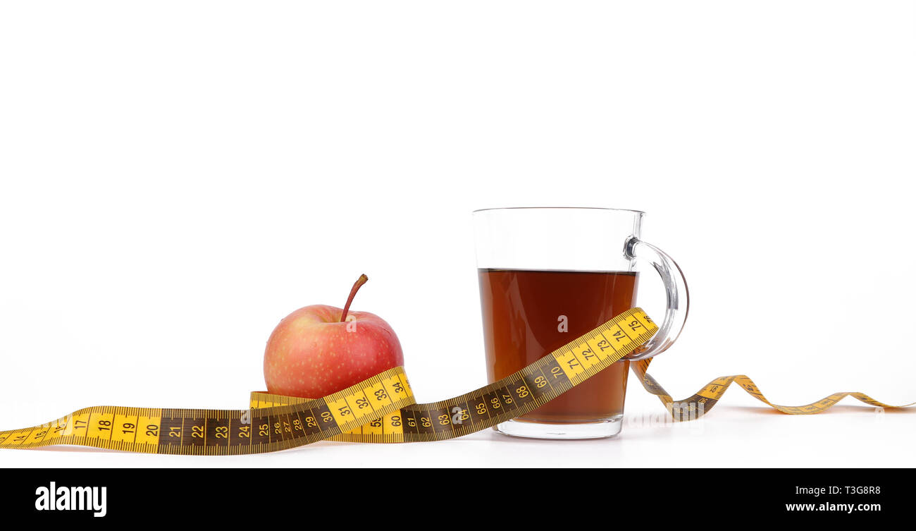 Slimming with tea and fruits, a cup with tea and a measuring tape and a delicious red apple isolated on white background - Stock Image