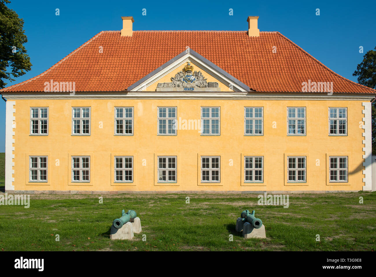 The colourful Commander's House in Kastellet, Copenhagen with its yellow-dressed masonry, white detailing, red tiled roof and decorated pediment. - Stock Image