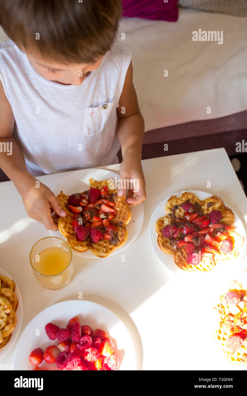 Sweet birthday boy, eating belgian waffle with strawberries, raspberries and chocolate at home Stock Photo