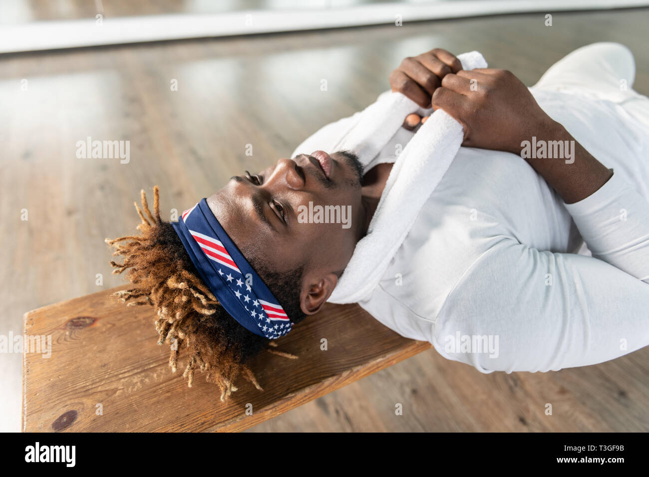Tired good-looking guy with colorful bandanas lying on wooden seat - Stock Image