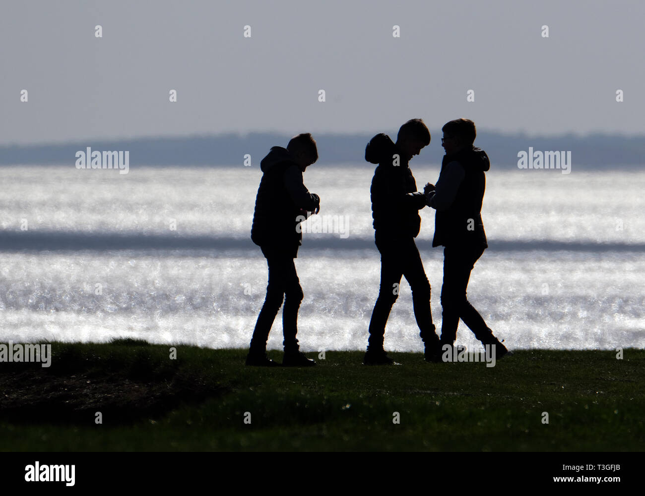 Group of lads in silhouette on cliff top. - Stock Image