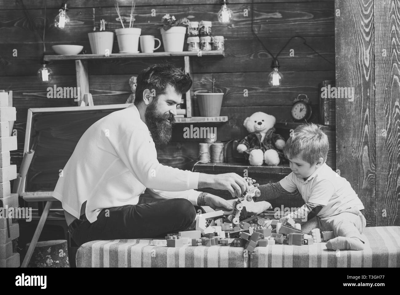 Father and happy son play with constructor. Fatherhood concept. Nursery with toys and chalkboard on background. Family playing with constructor at - Stock Image