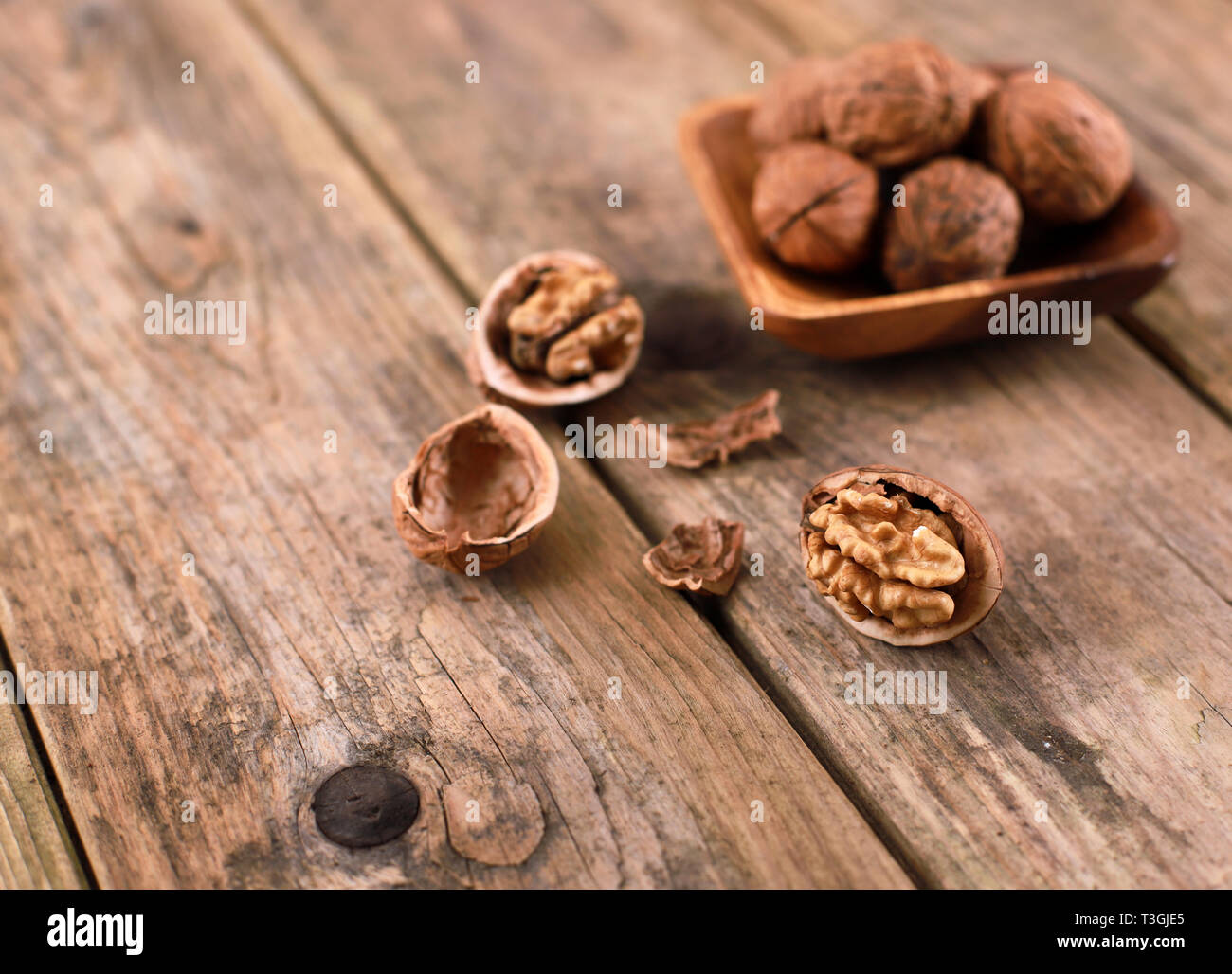 walnuts on a rustic wooden table - close up - walnuts broken up and closed - Stock Image