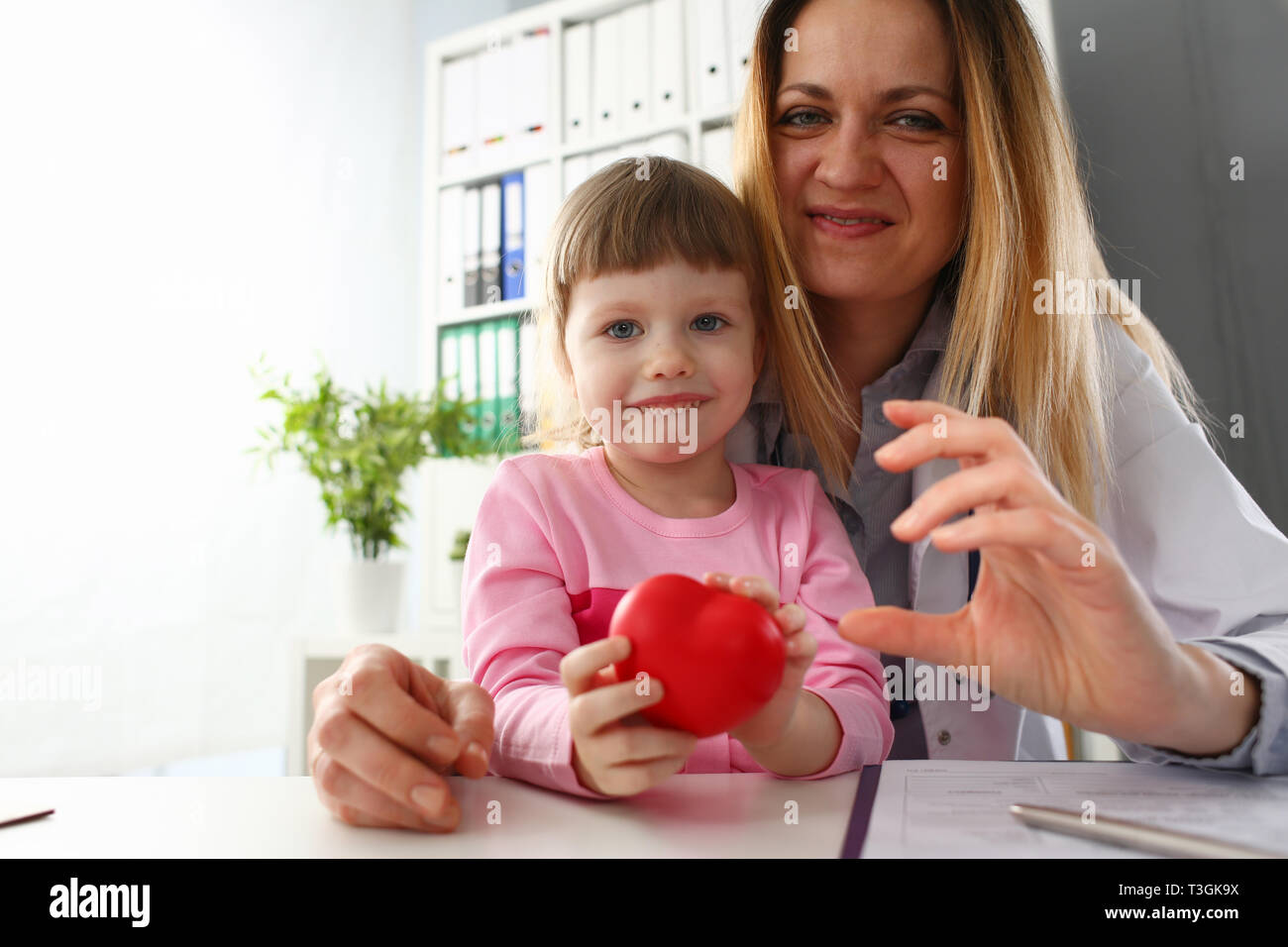 Little baby girl visiting doctor holding in hands red toy heart - Stock Photo