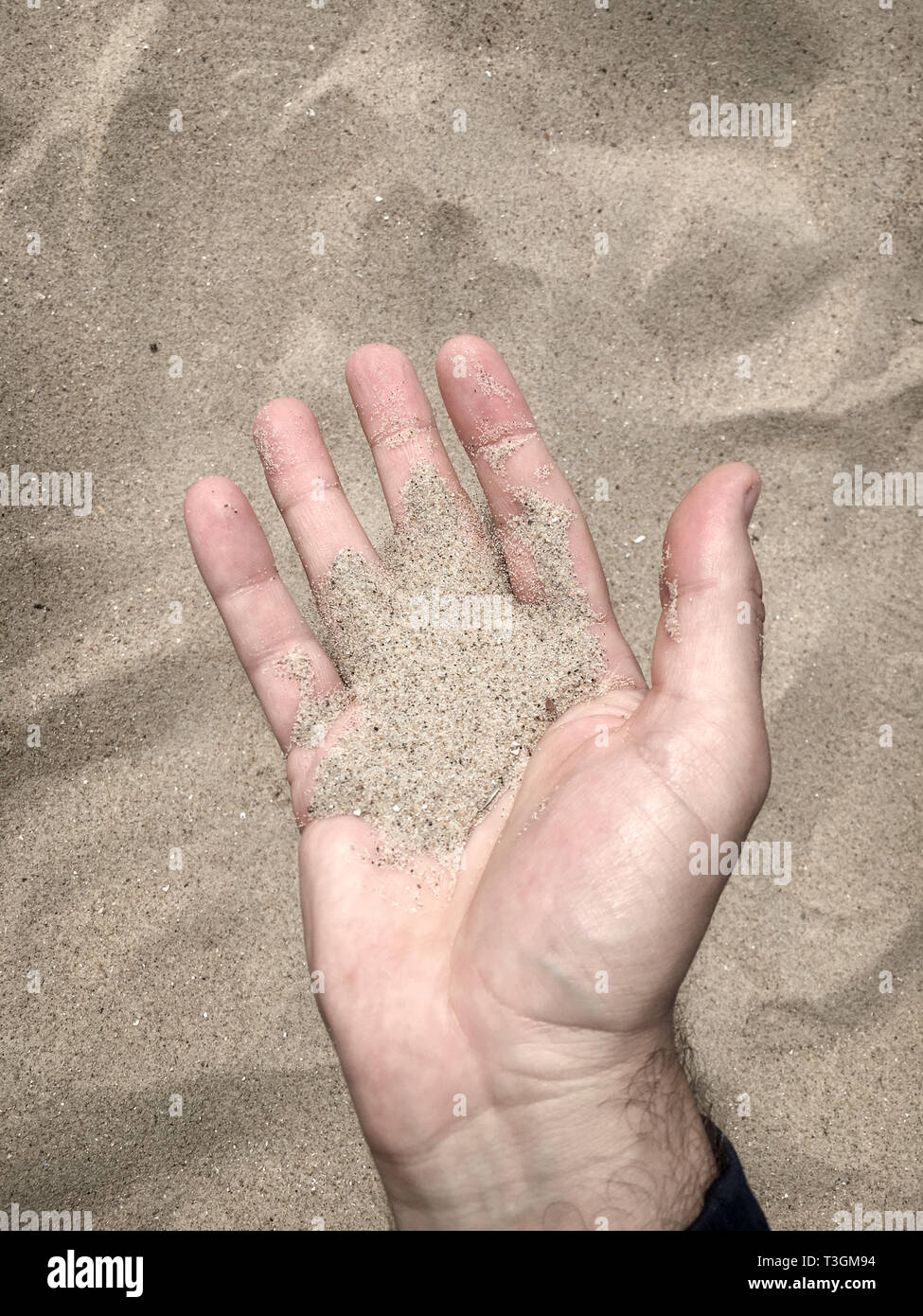 Man having sand in his open hand - Stock Image