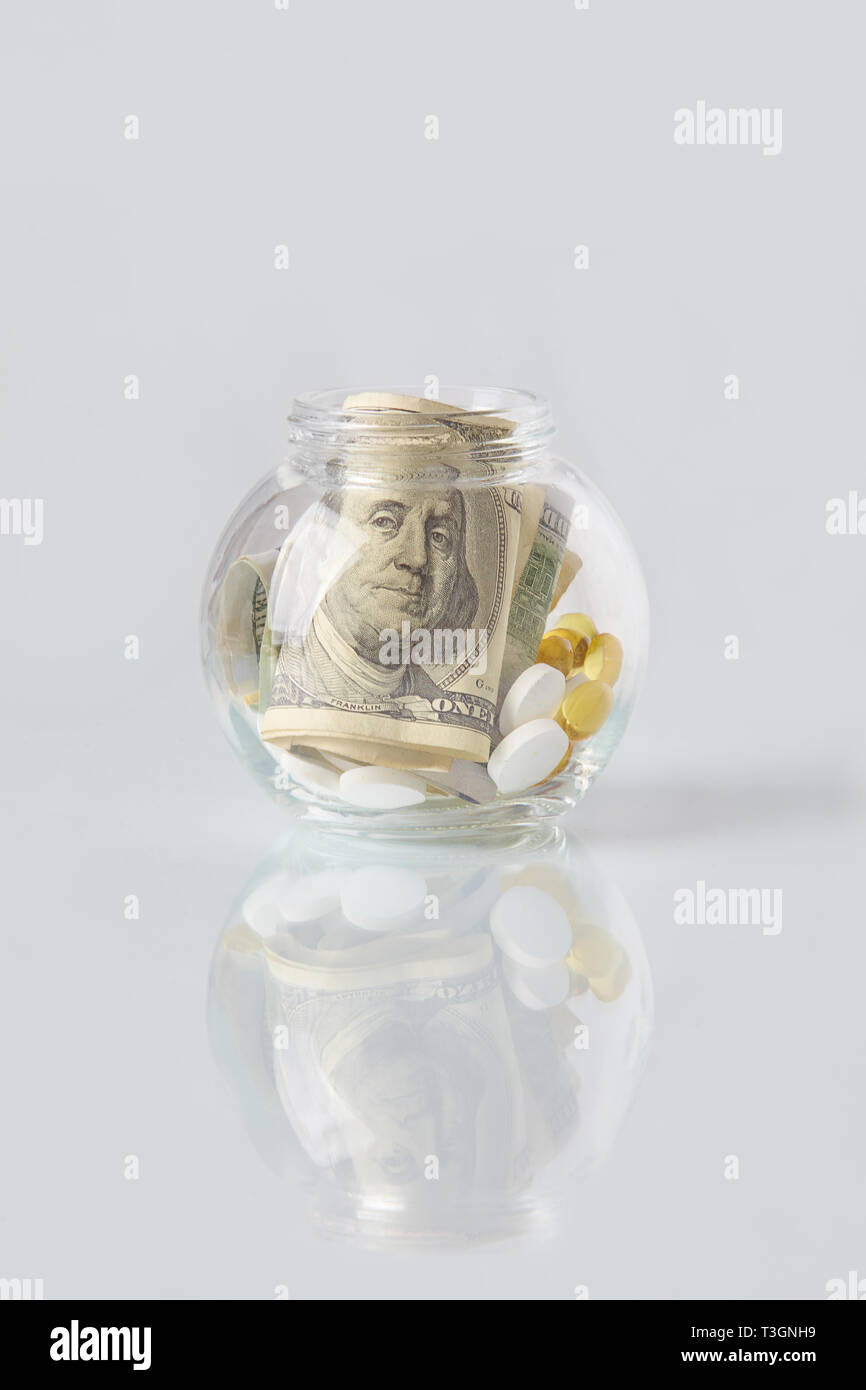 Pills and dollar bills in a glass bottle on a glass table. Medical or pharmacy prescription for health. Business, finance concept. Cost of the healthy Stock Photo