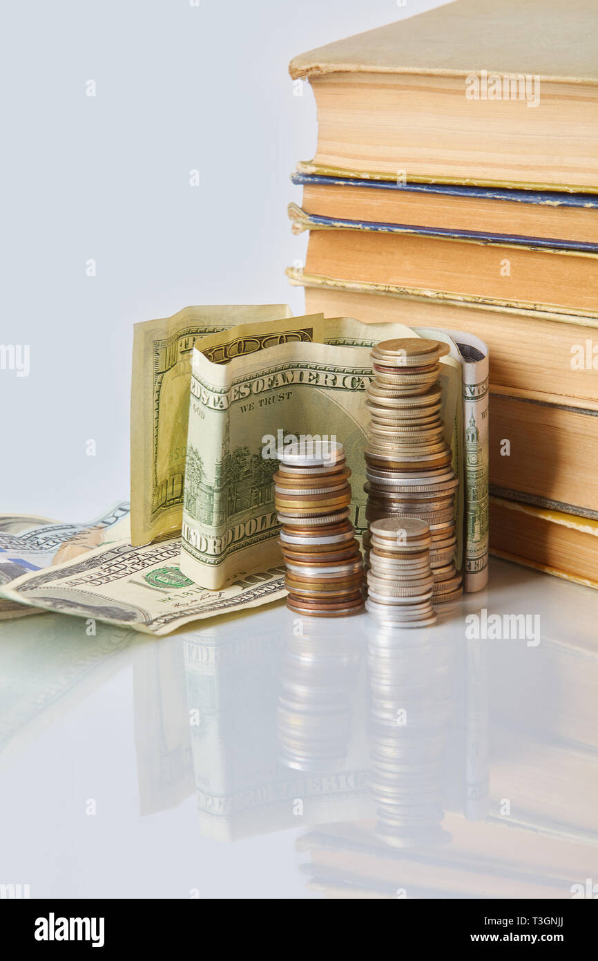 Financial education  concept - money: bills, coins, old books on a glass table. - Stock Image