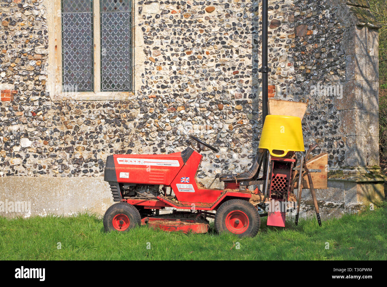 A motor mower with gardening maintenance equipment in the churchyard at Hassingham, Norfolk, England, United Kingdom, Europe. - Stock Image