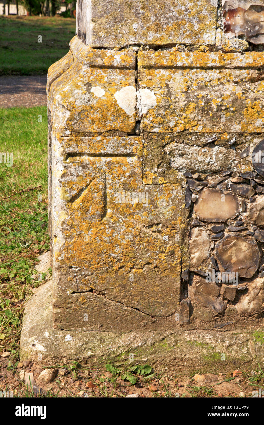 A bench mark at the base of the Church tower in Strumpshaw, Norfolk, England, United Kingdom, Europe. - Stock Image