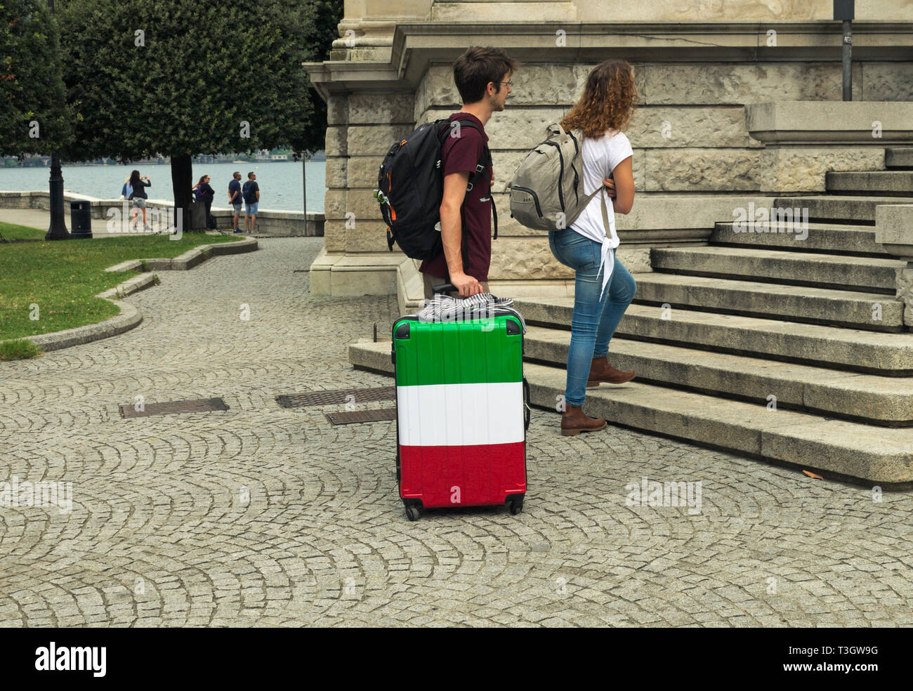 couple of young tourists with luggage and backpack in Como, Italy - Stock Image