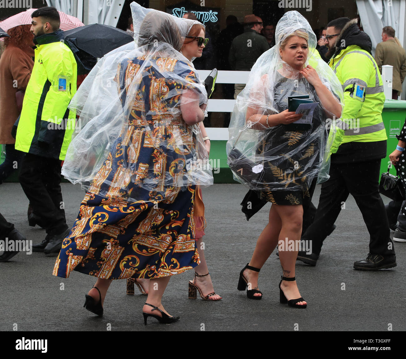 Racegoers shelters from the rain in plastic ponchos at day one of the 2019 Randox Health Grand National Festival at Aintree Racecourse in Liverpool. - Stock Image