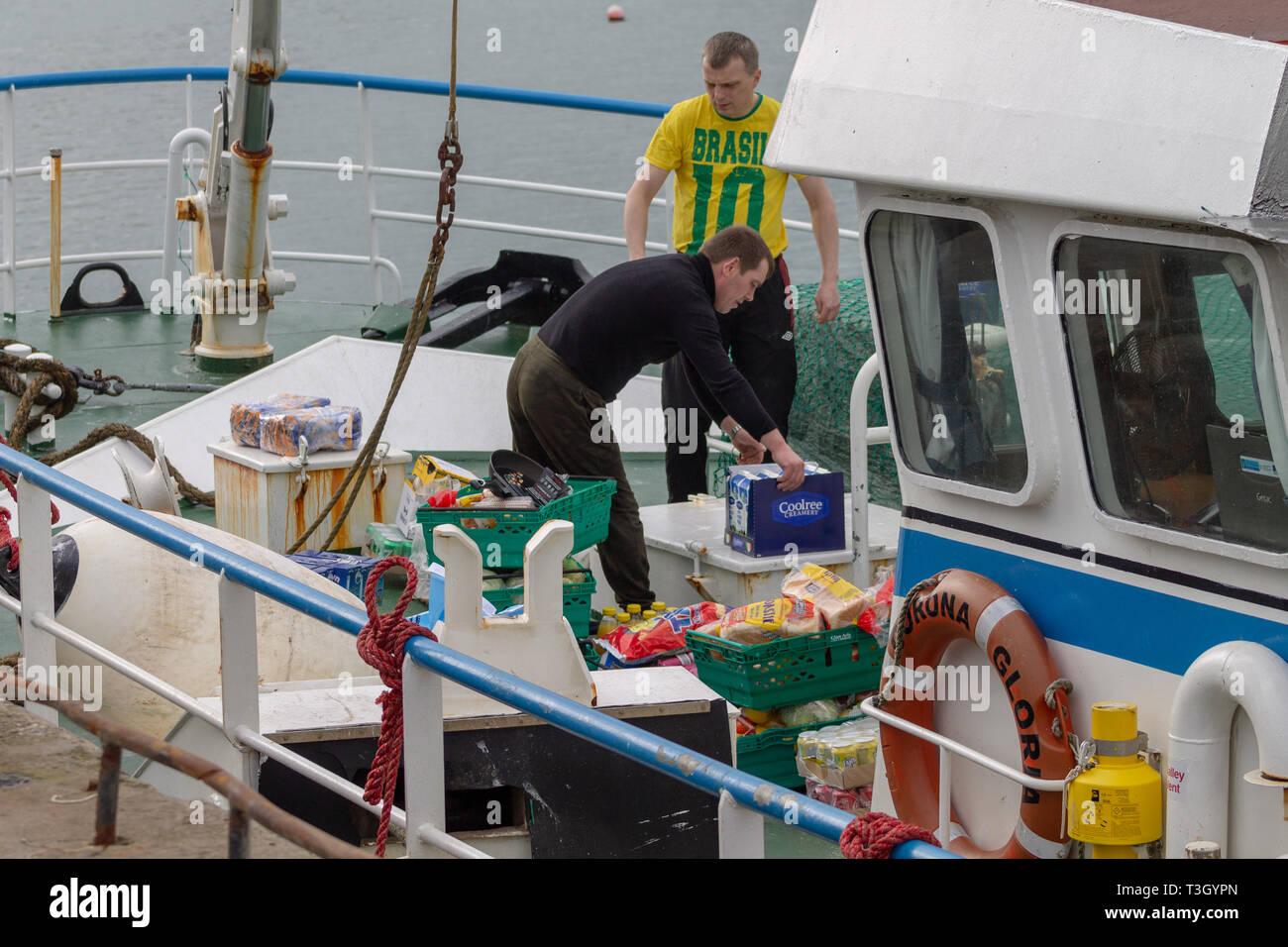trawler crew re provisioning or restocking food storing ship. - Stock Image