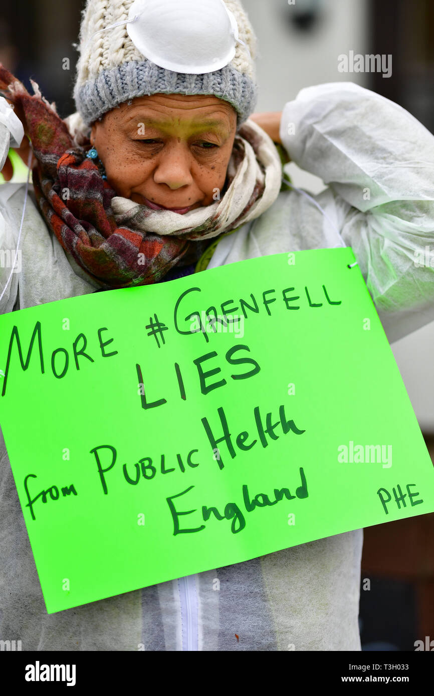 An activist in a hazmat suit and mask stops traffic in west London in a protest accusing authorities of lying after cancer-causing chemicals were found in soil close to Grenfell Tower. - Stock Image