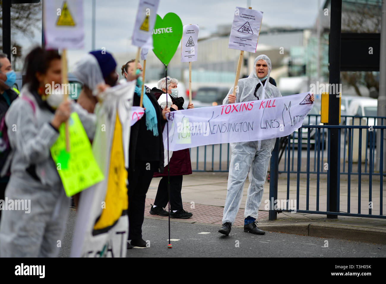 Activists in hazmat suits and masks stop traffic in west London in a protest accusing authorities of lying after cancer-causing chemicals were found in soil close to Grenfell Tower. - Stock Image