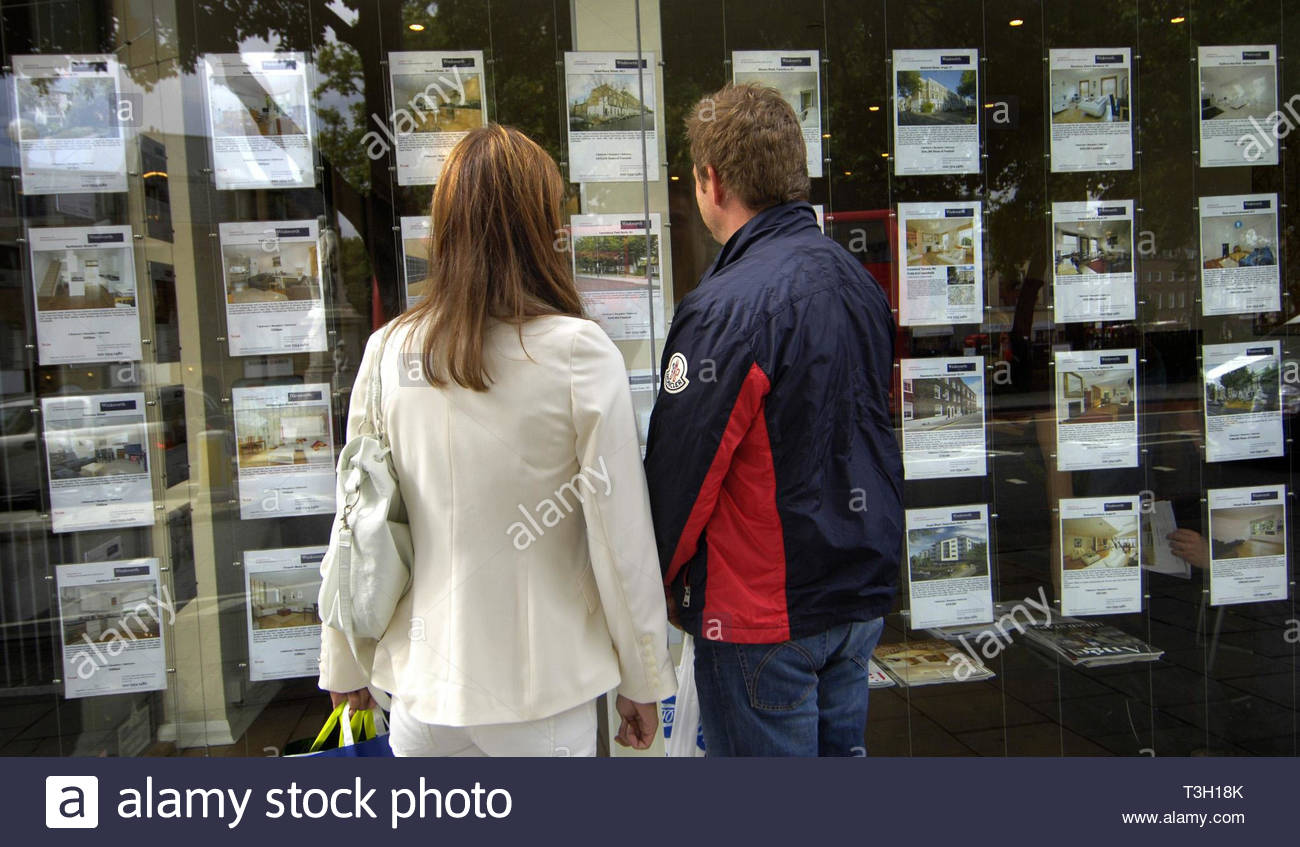 File photo dated 02/09/08 of people standing outside an estate agent's window. First-time buyers face a typical decade-long wait to save enough money to get on to the property ladder - rising to 15 years in London - research suggests. - Stock Image