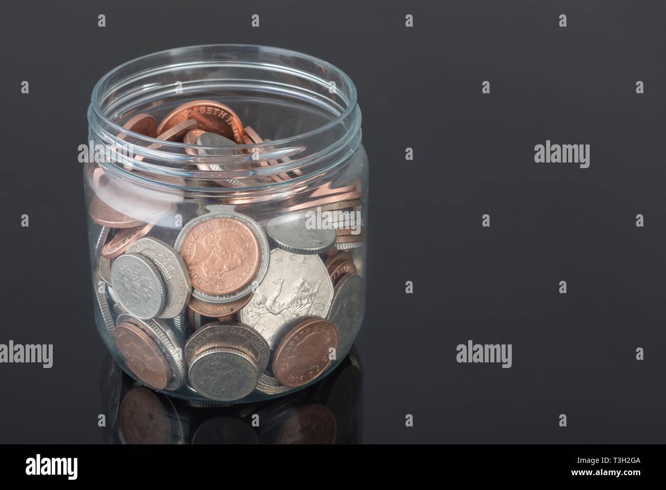Plastic pot containing UK coins - as metaphor for personal savings, rainy day saving, pensions savings pot. - Stock Image