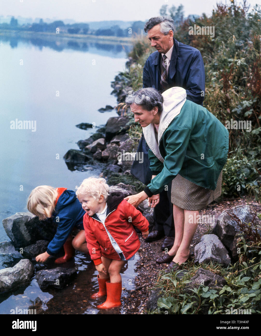 Two young children,with their grandparents,are intrigued by the river.The young boy loves to throw stones into the water. - Stock Image