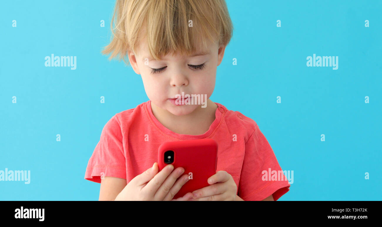 Child tapping cell phone screen, interest in modern technology - Stock Image