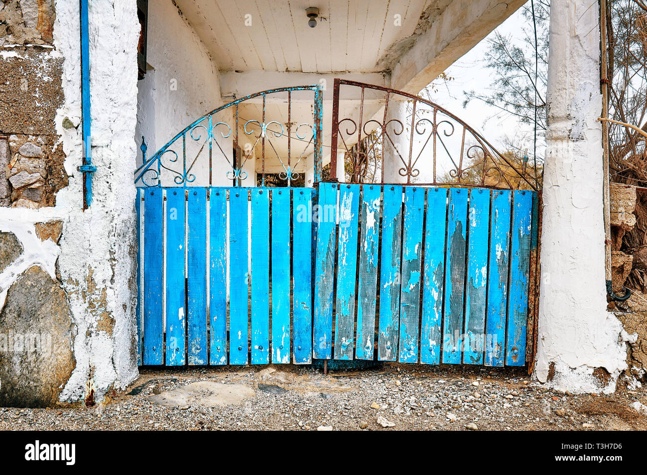 Retro wooden and rusty wrought iron blue entrance fence door of a rural house - Stock Image