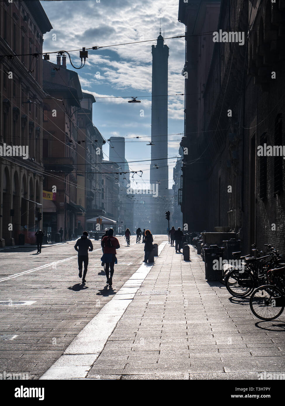 Sunday Morning runners in Bologna City Centre with the Twin Towers, Garisenda Tower and the Asinelli Tower in the distance. - Stock Image