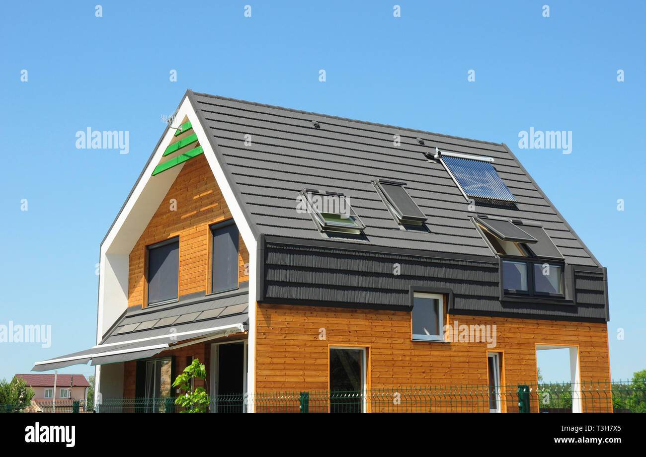 Modern Passive House Exterior. Modern energy efficiency house with skylight windows and solar panels on the roof top. - Stock Image